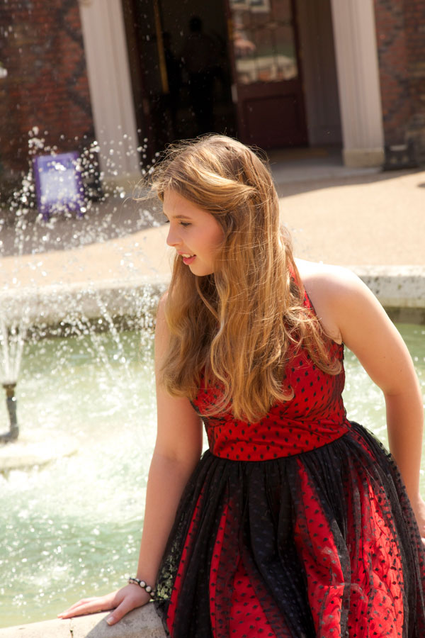Nikita sitting by the fountain in her prom dress