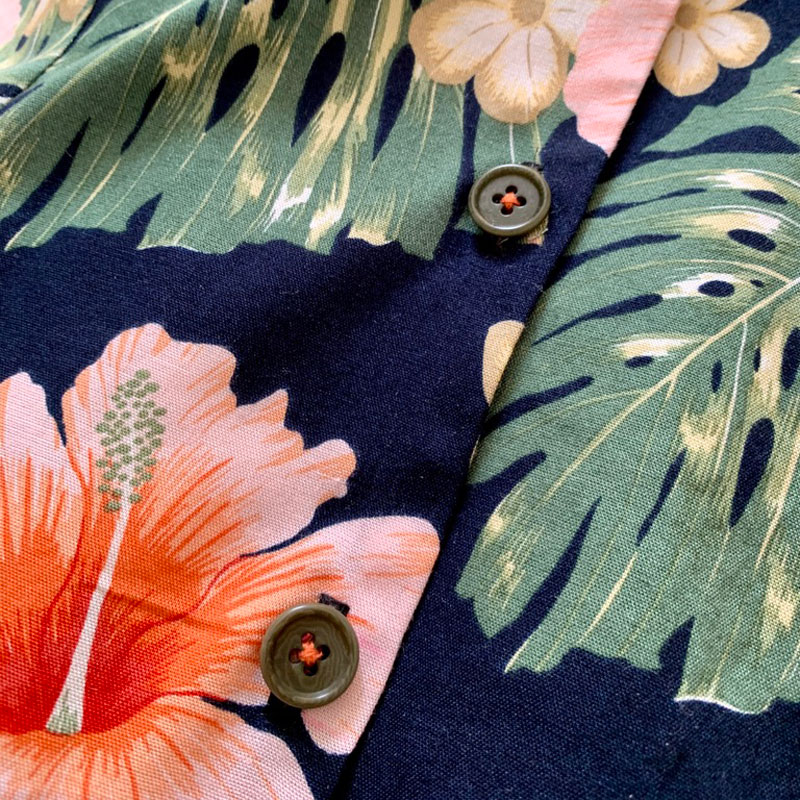close up of buttons sewn on with orange thread